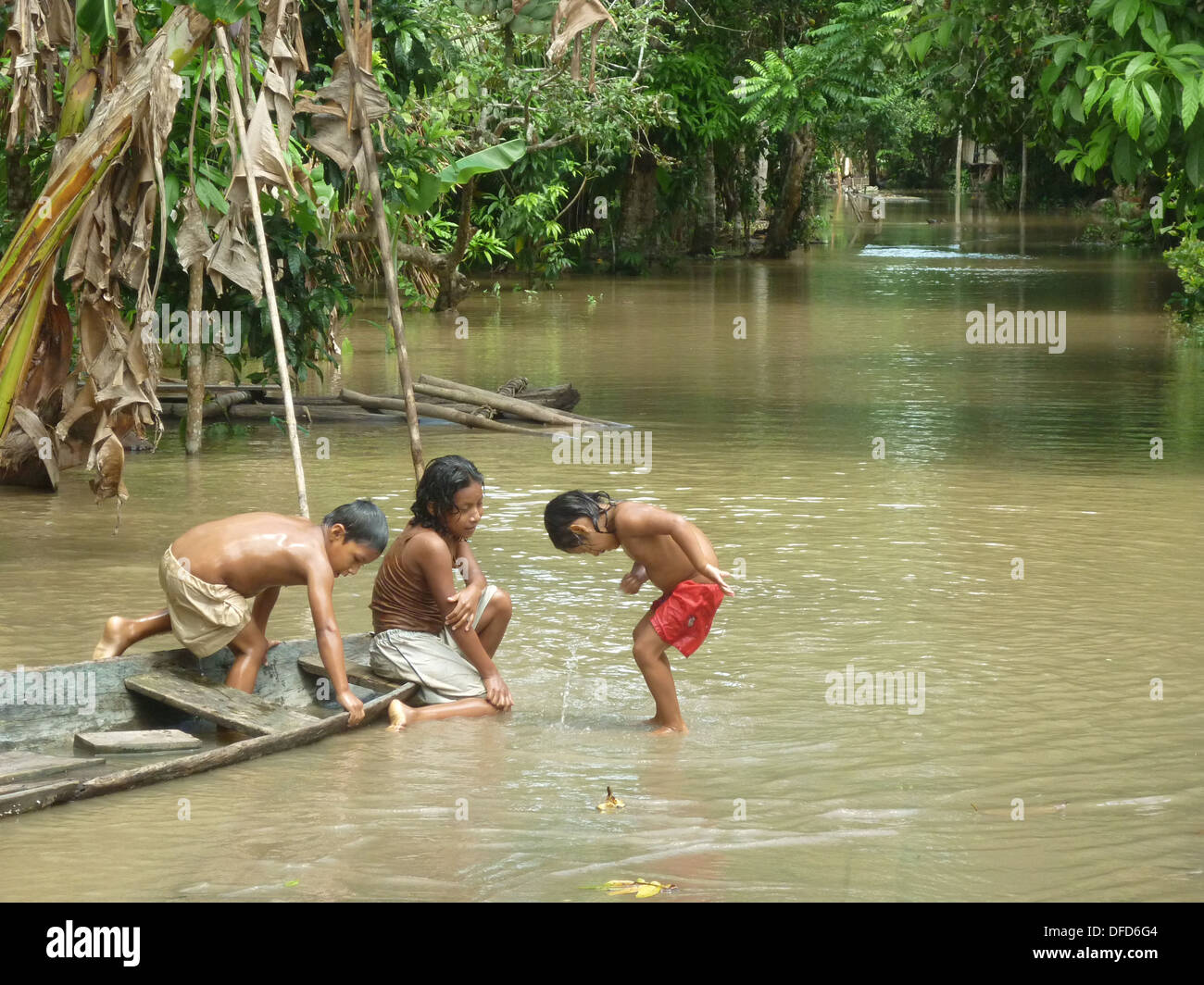 Children of the Yagua Tribe play with a wooden canoe in ...