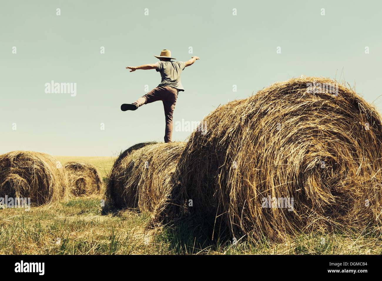 Back view of a man balancing on one leg on top of a hay bale. Stock Foto