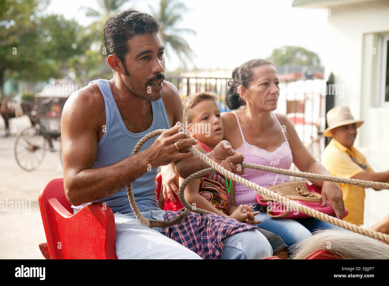 A cuban family comprising mother, father and son, in a horse and carriage, Havana, Cuba, Caribbean Stock Foto