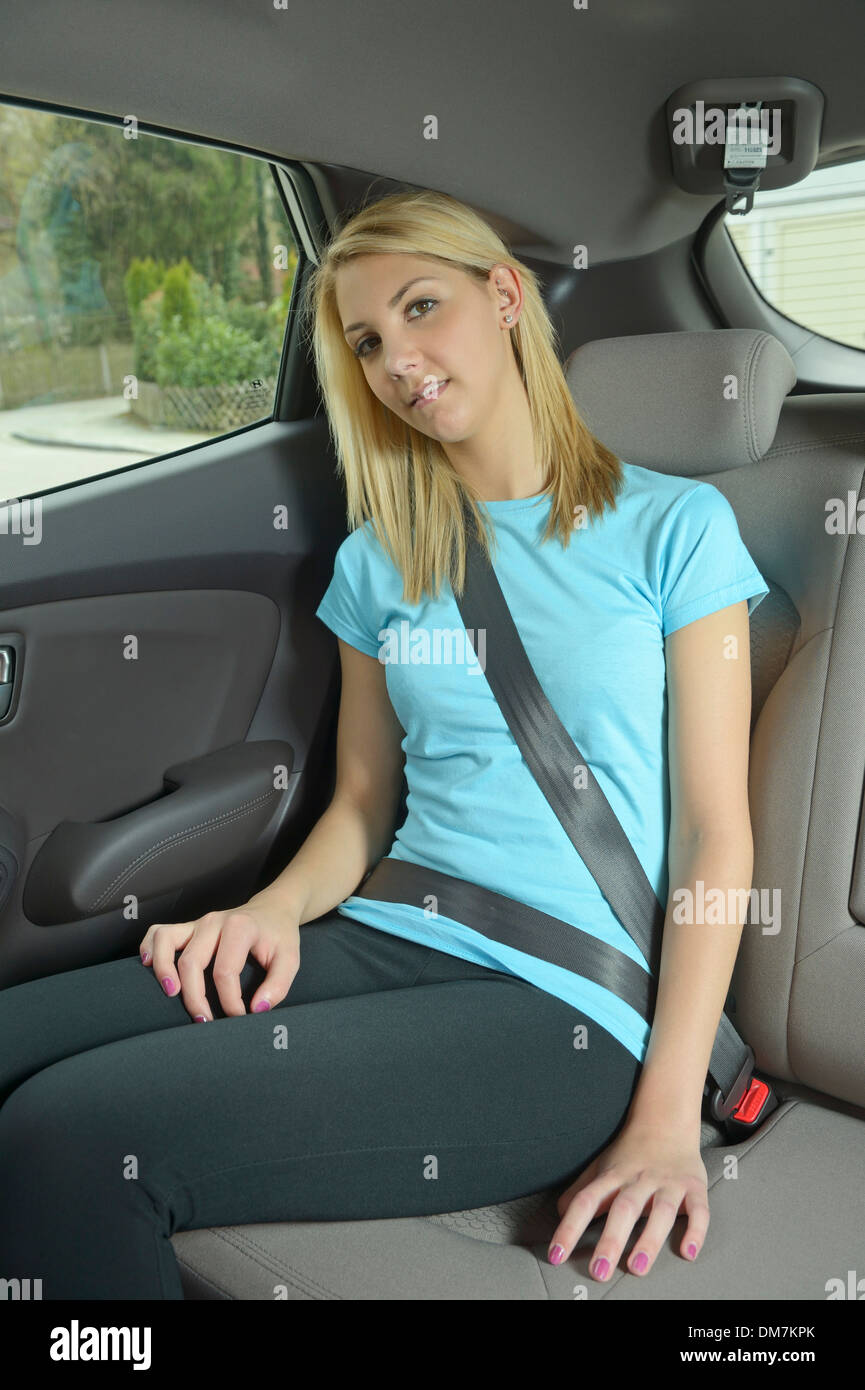 Young Woman Buckled Up Sitting In The Back Seat Of A Car