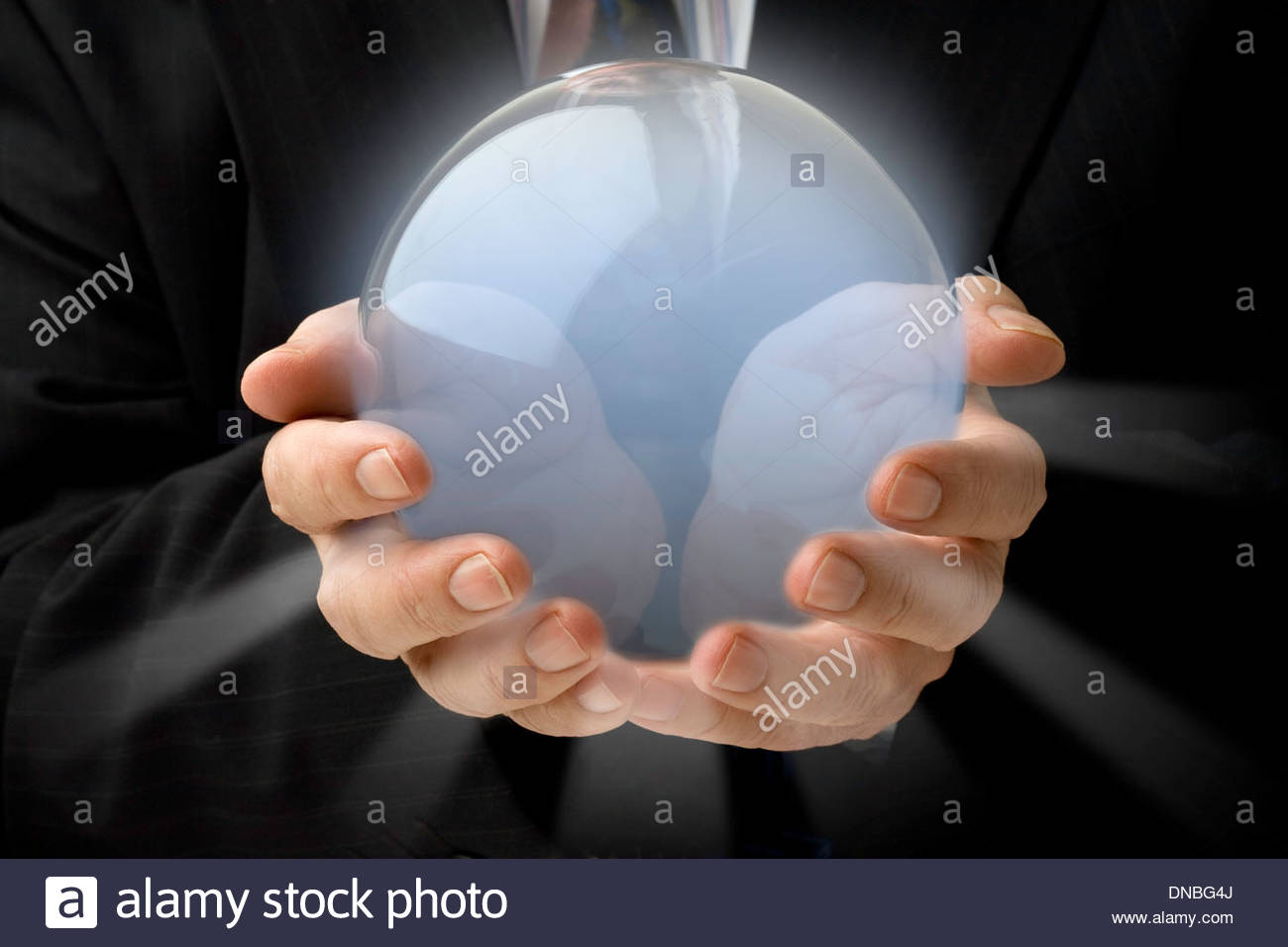 Technology Management Image: Businessman Holding A Glowing Crystal Ball In Both Hands
