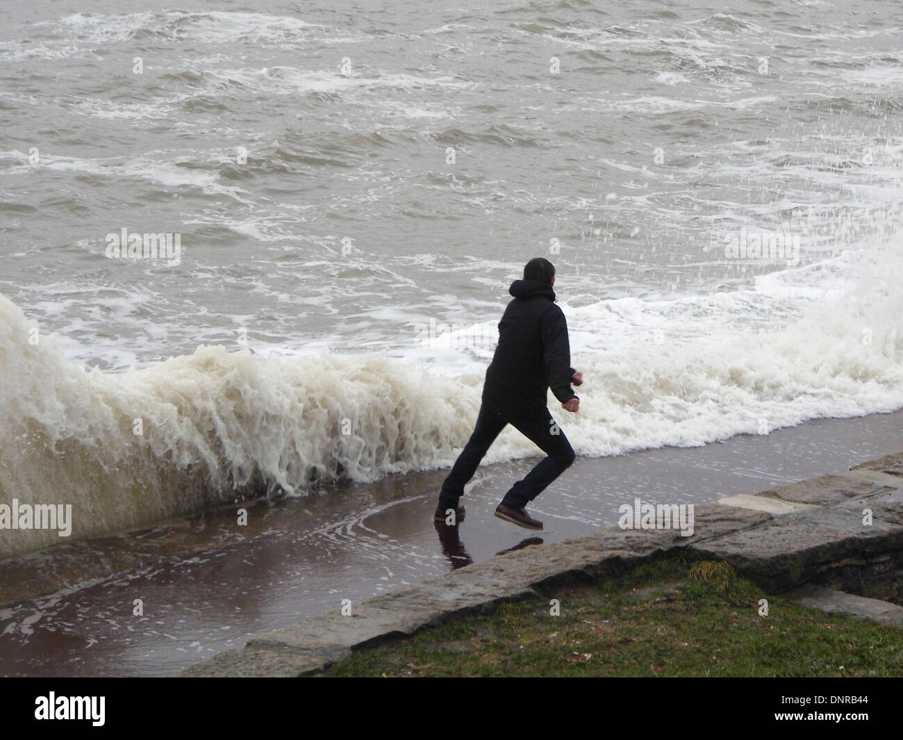 portsmouth-england-4th-january-2014-a-man-plays-chicken-with-waves-DNRB44.jpg