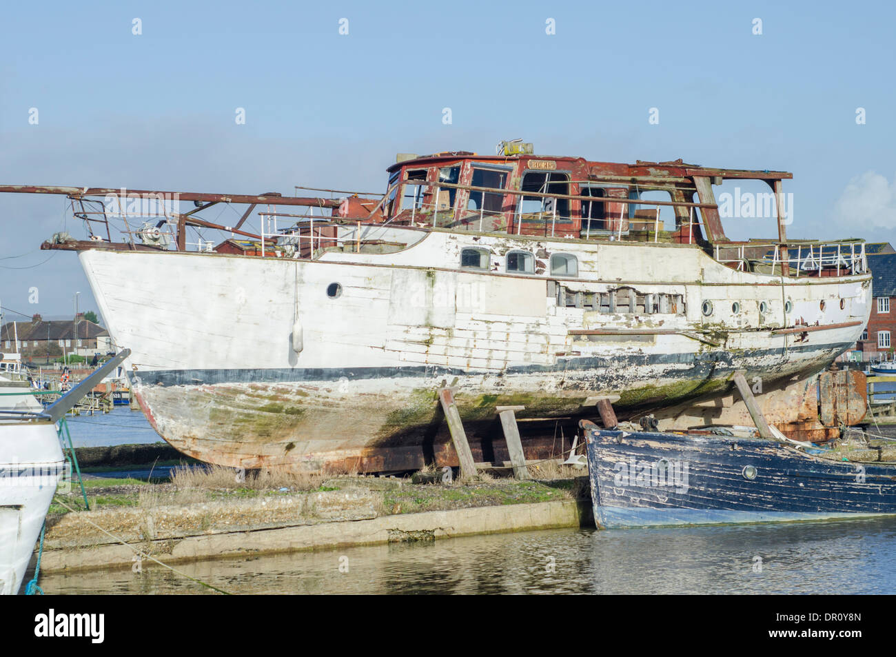 a-wooden-decaying-boat-out-of-the-water-by-a-river-DR0Y8N.jpg