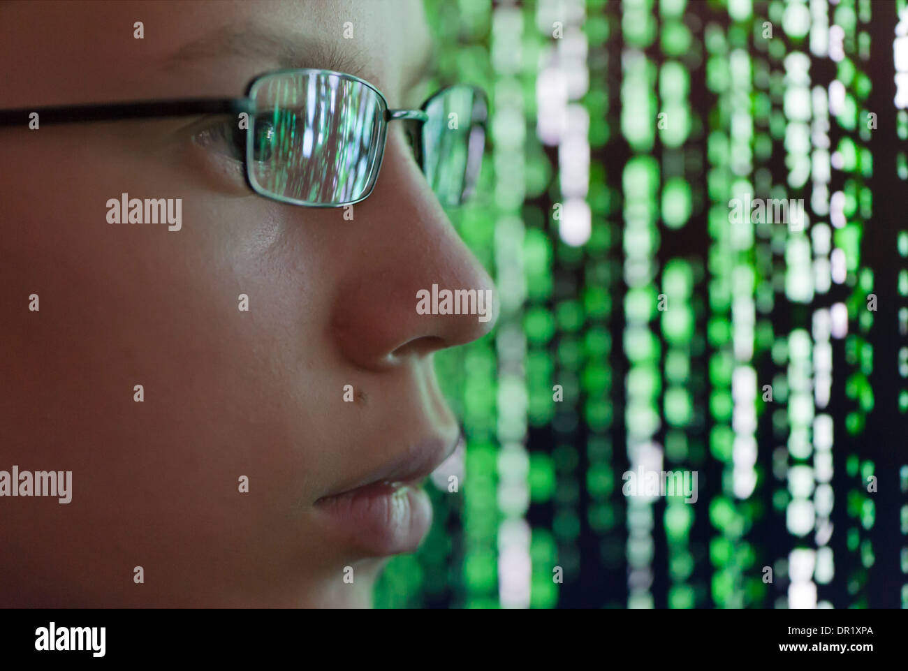 A young man with glasses is watching futuristic symbols on a computer screen. Symbols are reflecting in the man's Stock Photo