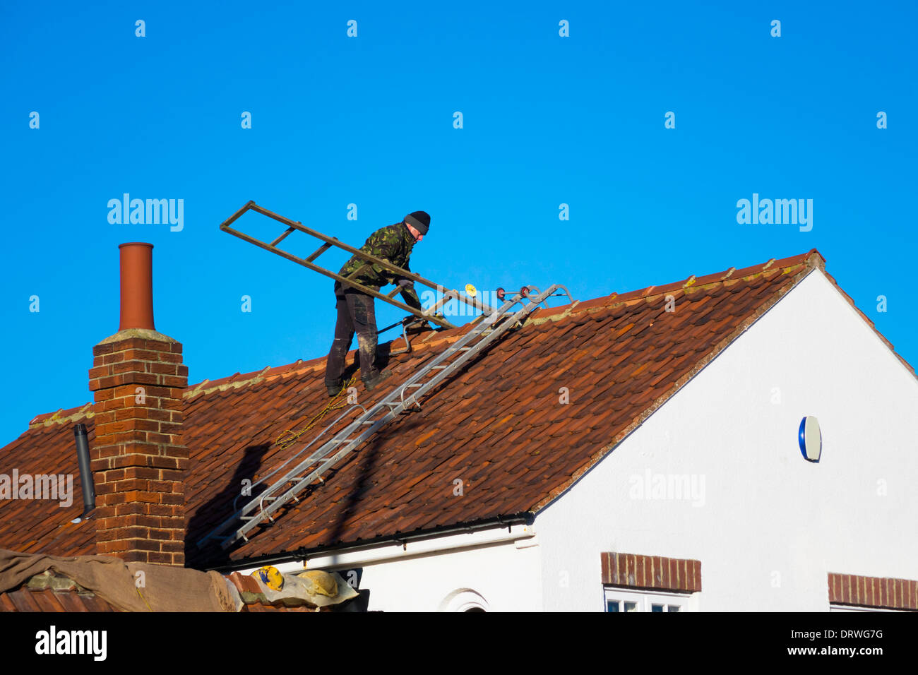 A Man On A House Roof Setting Access Ladders For Repair Of