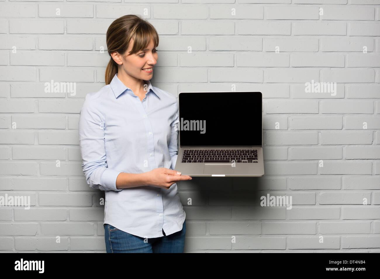Female pretty cheerful pointing computer studio Stock Foto