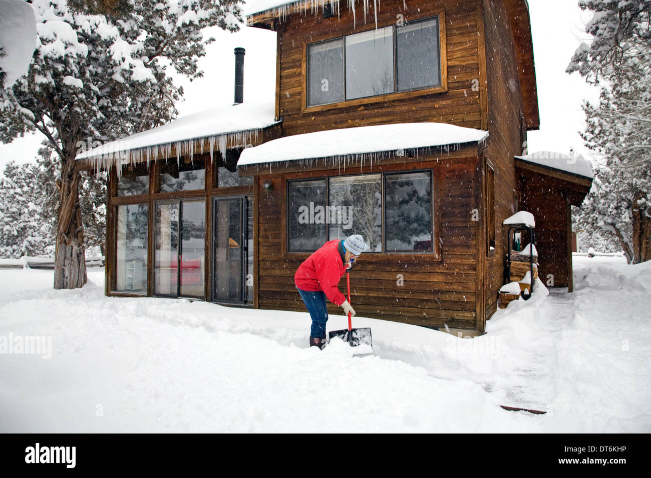 A Woman Shoveling Snow From Her Deck Or Front Porch At A