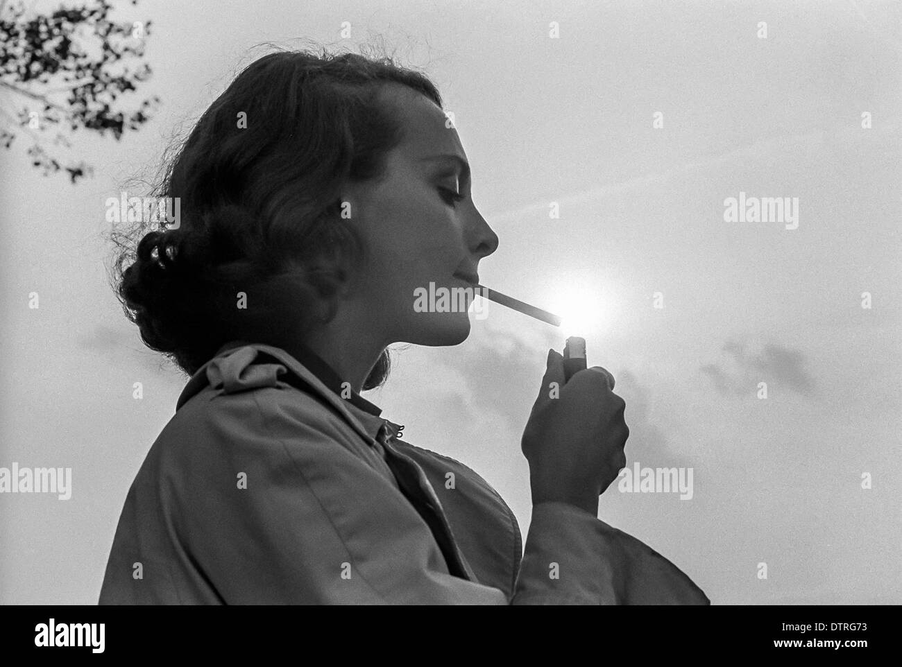 Young woman lighting a cigarette Stock Photo