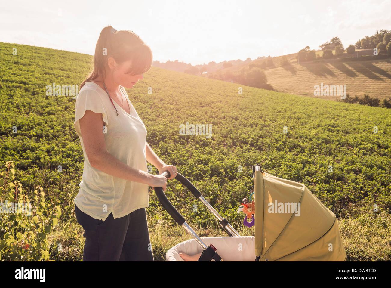 Mother strolling in countryside pushing baby pram Stock Foto