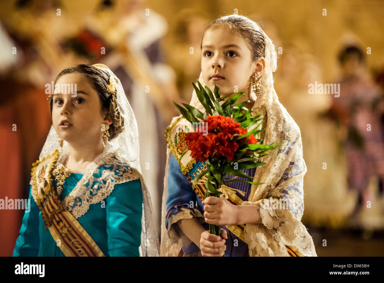 Valencia, Spain. March 18th, 2014: A little Fallera finally offers her flower bouquet to the Virgin and hands it Stock Foto