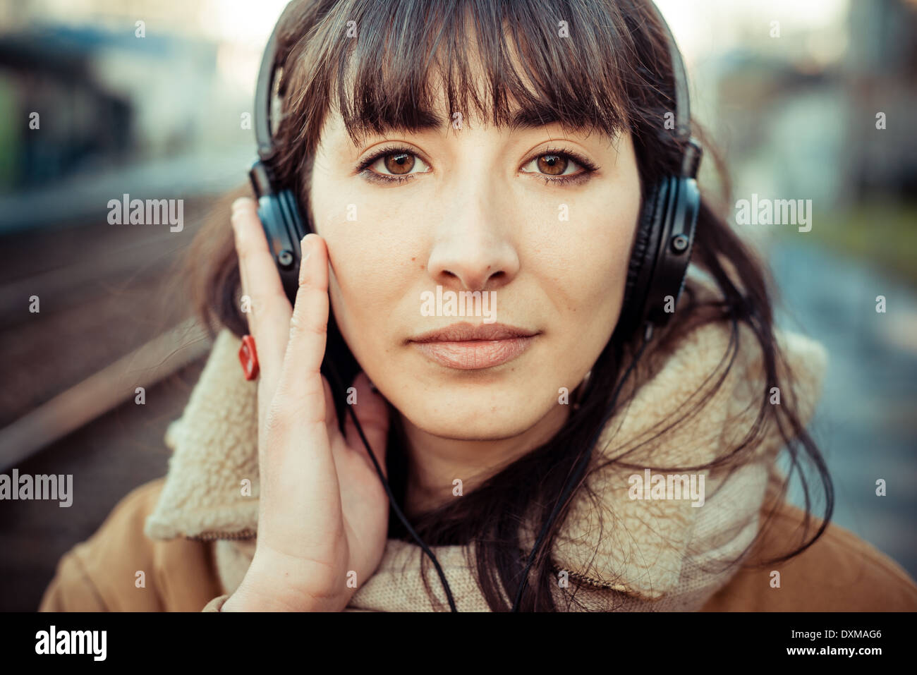beautiful young woman listening to music headphones in the city winter Stock Photo