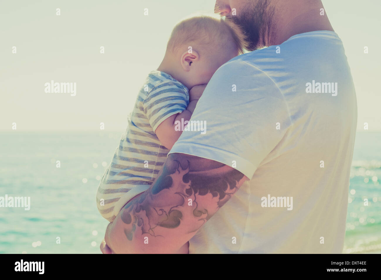 Close up of father holding baby son at beach Stock Foto