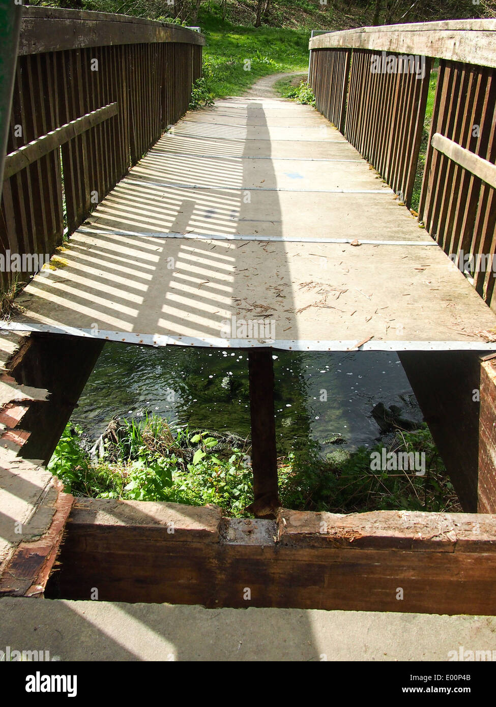 a-wooden-bridge-over-the-river-irk-in-manchester-with-boarding-missing-E00P4B.jpg