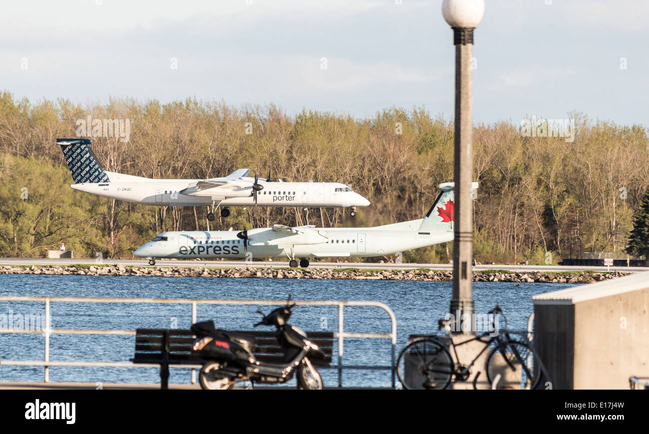porter plane landing flies over an air canada plane ready