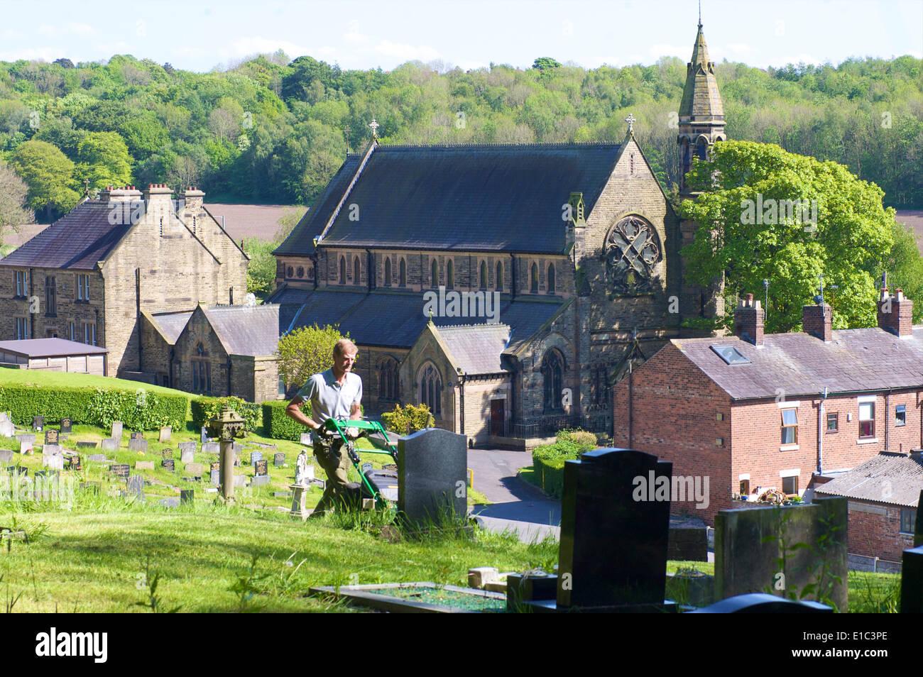 gardener-mowing-grass-in-cemetery-E1C3PE