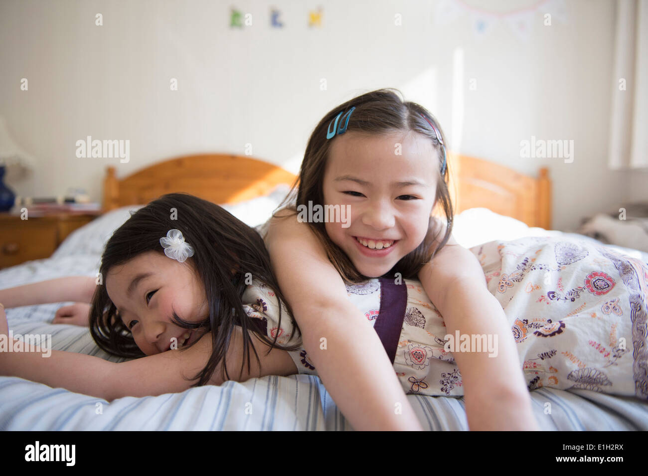 Two young female friends lying on bed Stock Foto