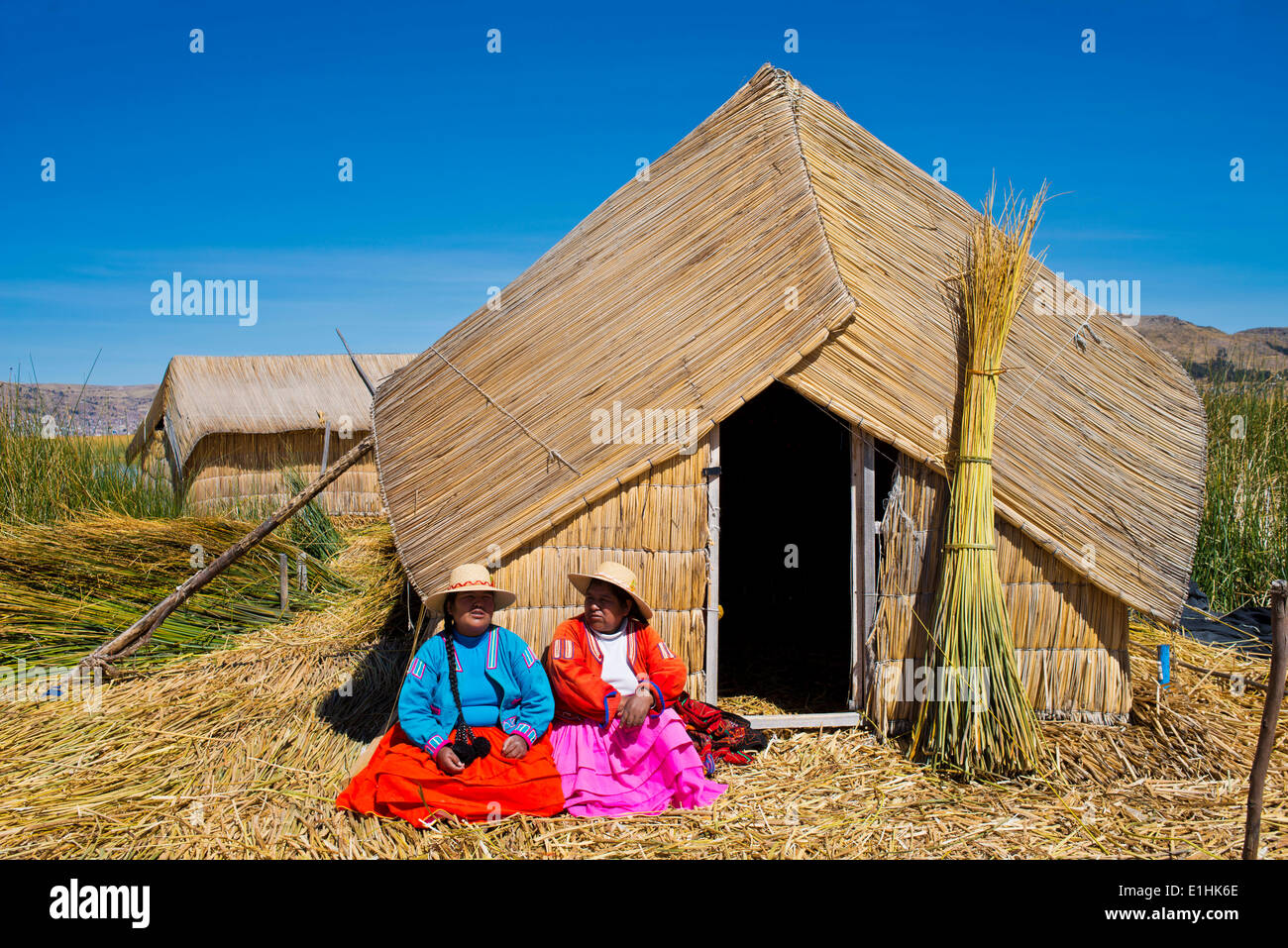 Two women of the Uro Indians wearing traditional dress sitting in front of a reed hut, floating islands made of Stock Foto