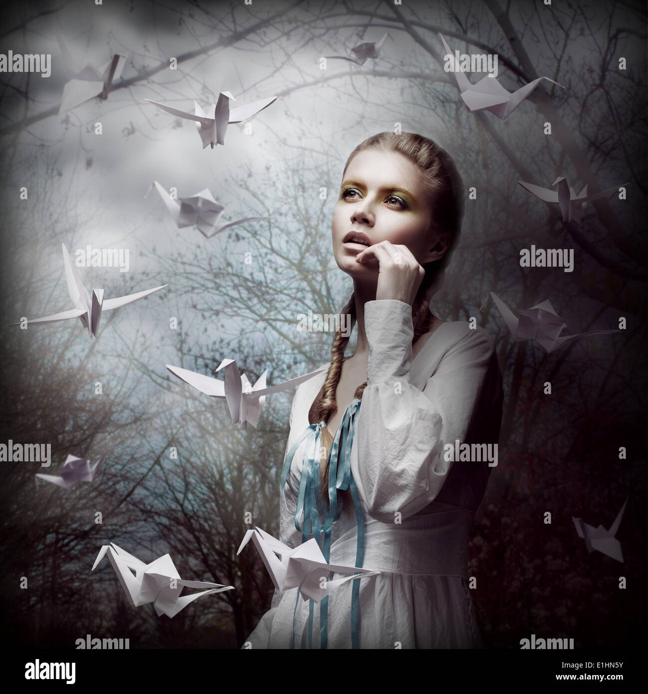 Inspiration. Woman with Flying White Origami Swans in Dark Mystic Forest Stock Foto