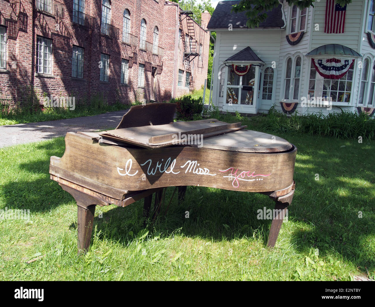 Broken old grand piano is left for trash on a front yard for Classic house piano