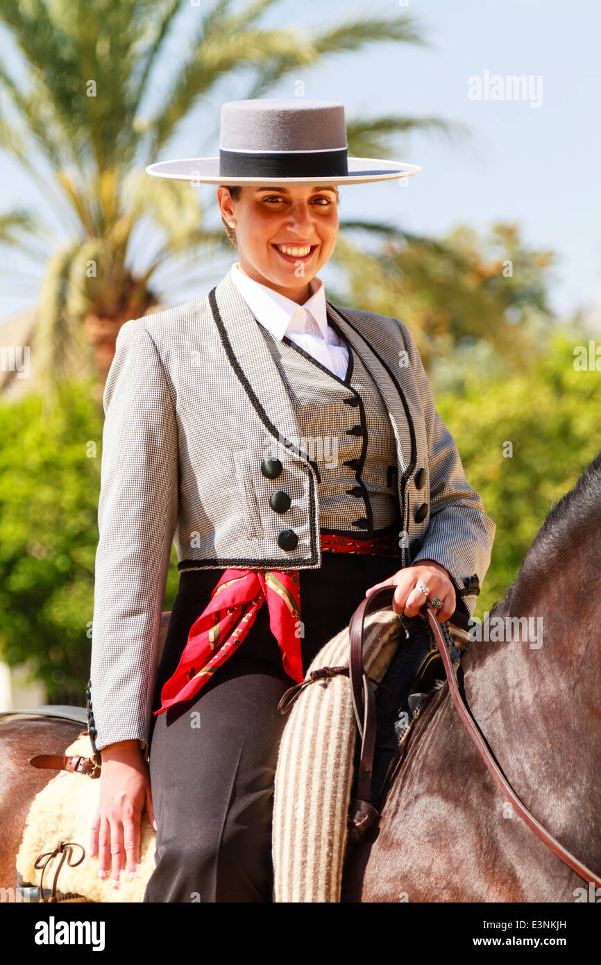 Female rider decked out in traditional flat-topped hat sitting on her horse smiling during Feria del Caballon. Stock Foto