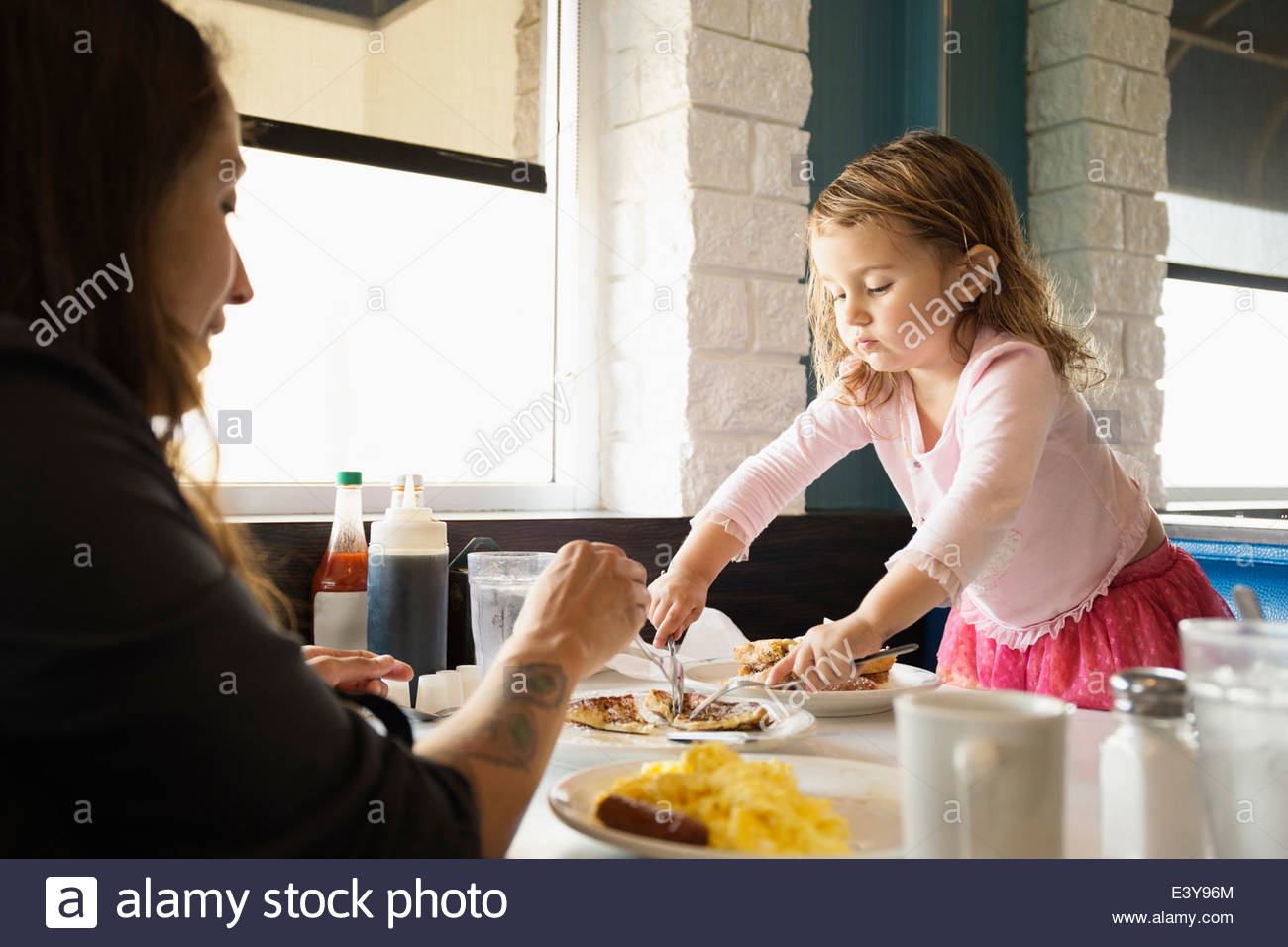 Mother and toddler daughter eating in diner Stock Photo
