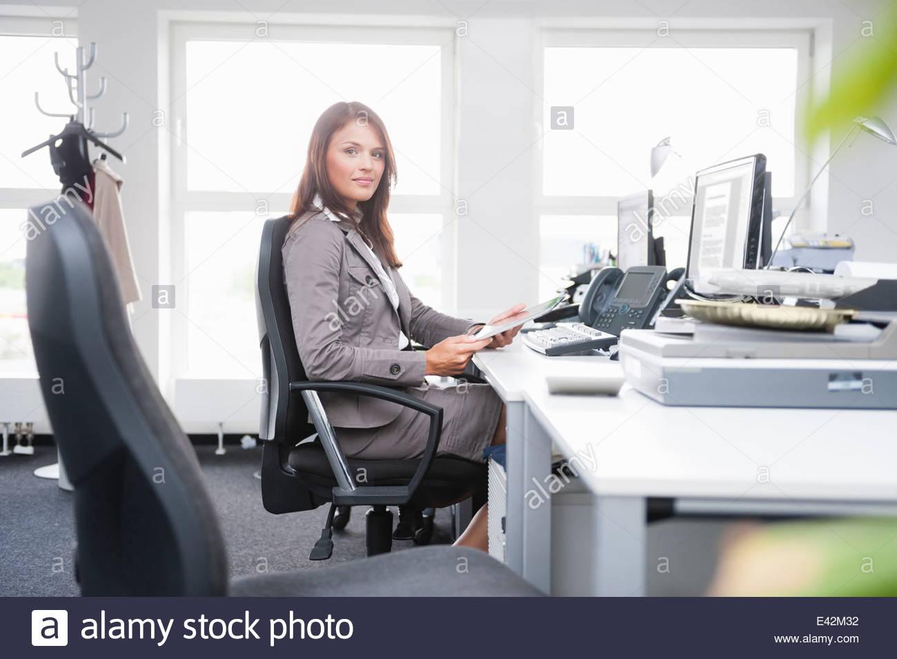 mid-adult-woman-sitting-at-desk-E42M32.j