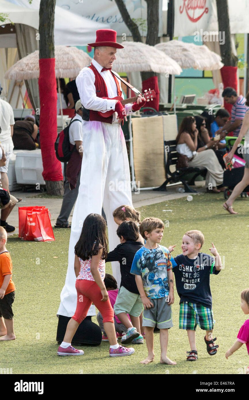man-on-stilts-dressed-in-red-and-white-playing-ukelele-while-children-E467RA.jpg