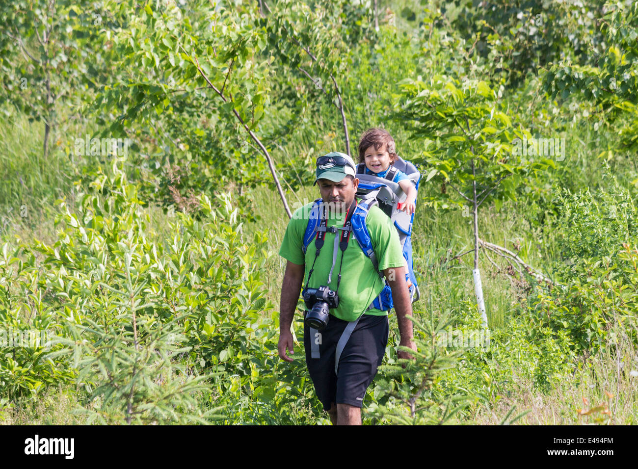 man-with-child-in-backpack-hiking-throug