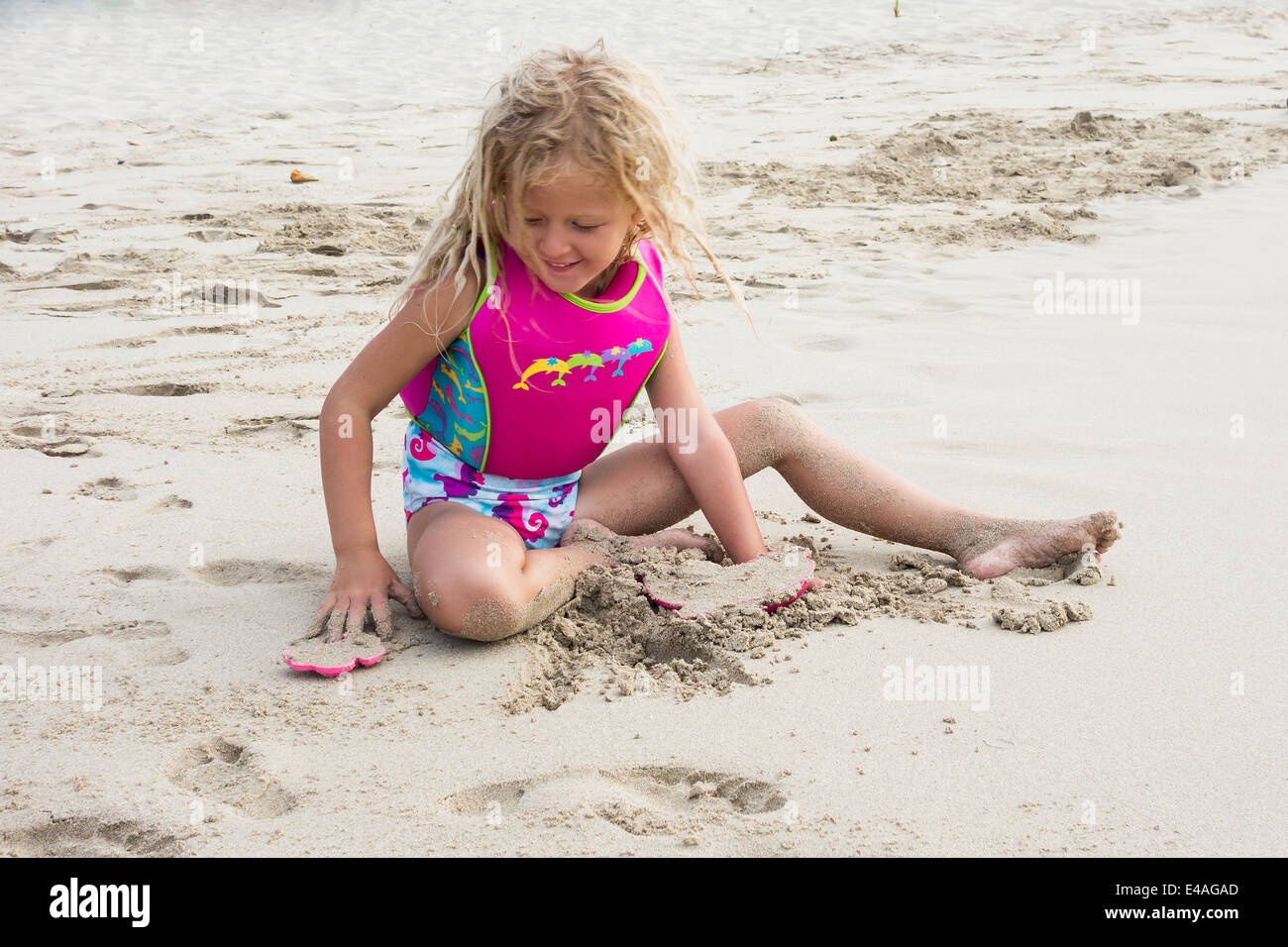 A 5 Year Old Blond Caucasian Girl Plays With Plastic Sand