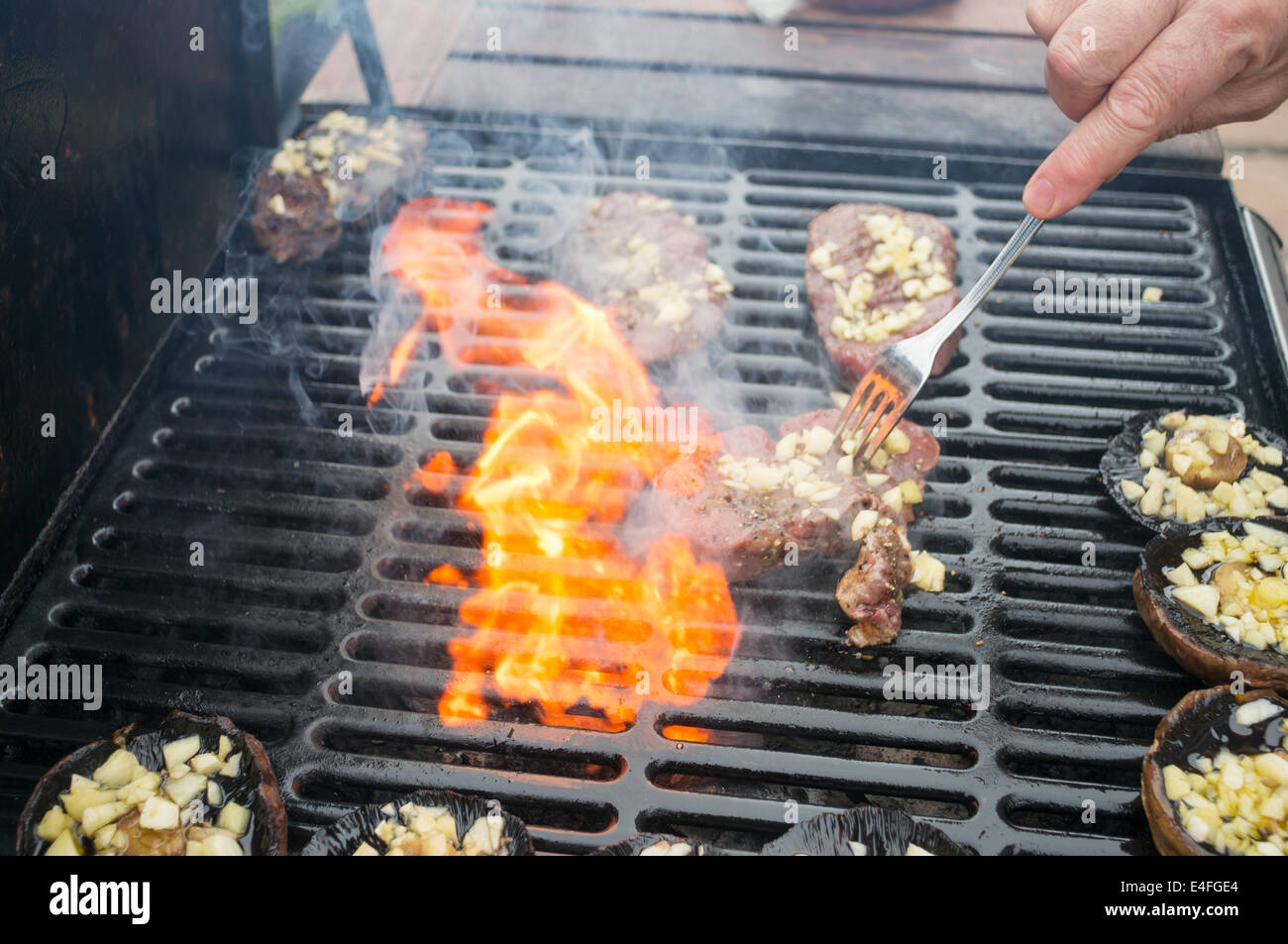 man-barbecuing-steak-and-mushrooms-with-