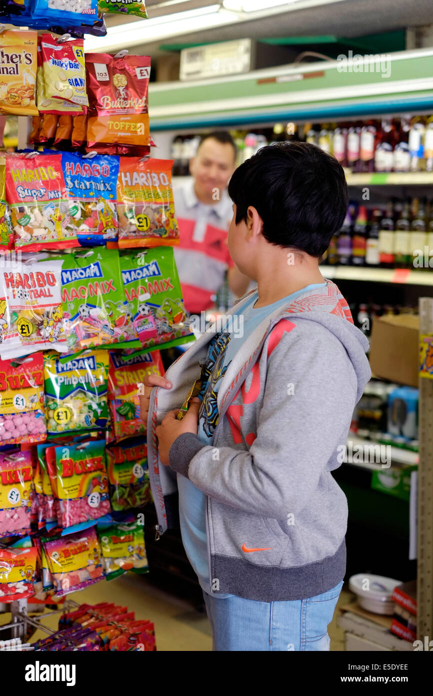 young boy shoplifting sweets in a small mini market Stock Photo
