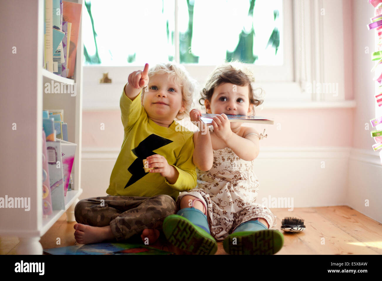 Female and male toddler friends pointing and looking up Stock Foto