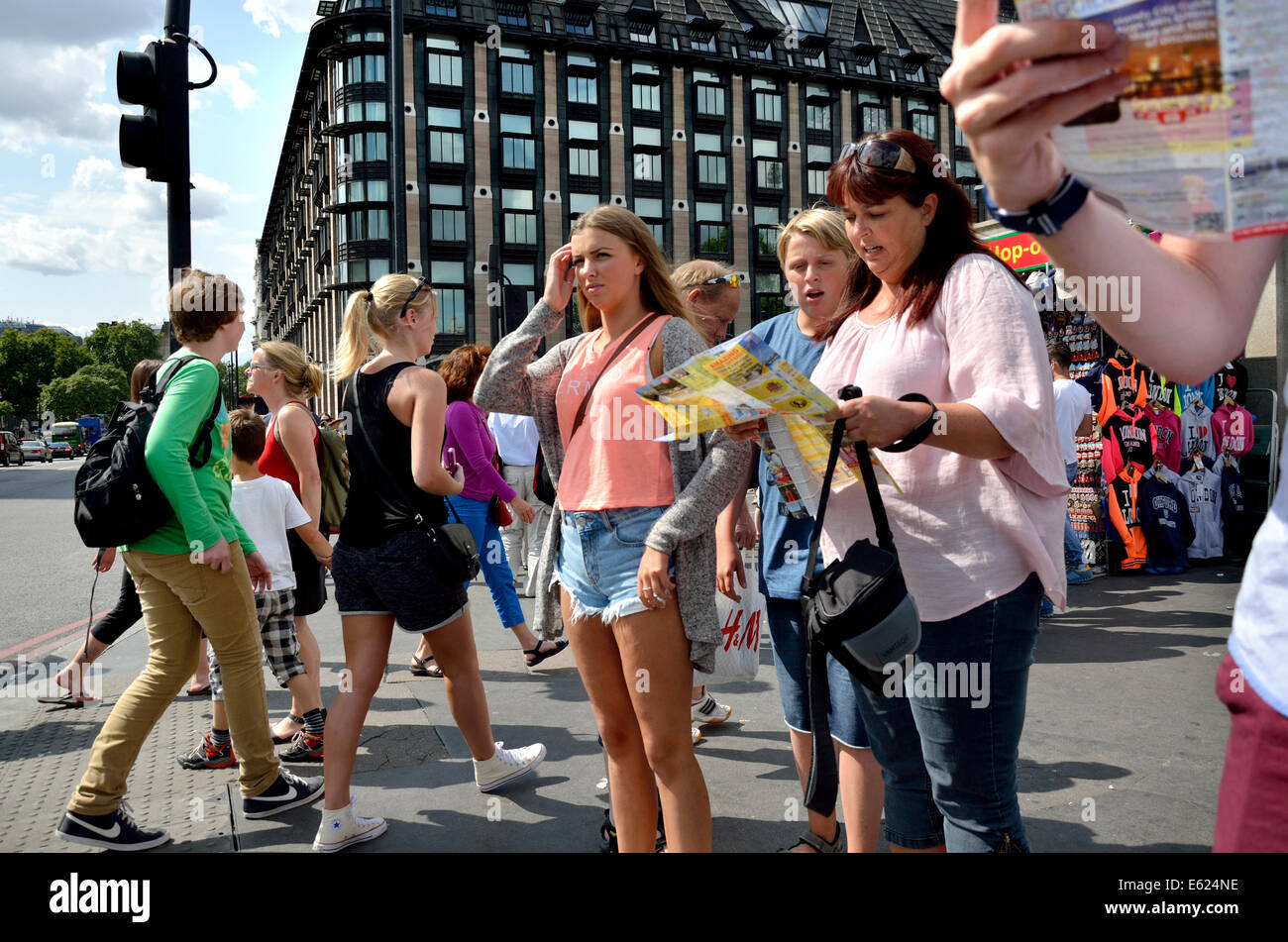 London, England, UK. Family looking at a map on Westminster Bridge - Portcullis House behind Stock Foto