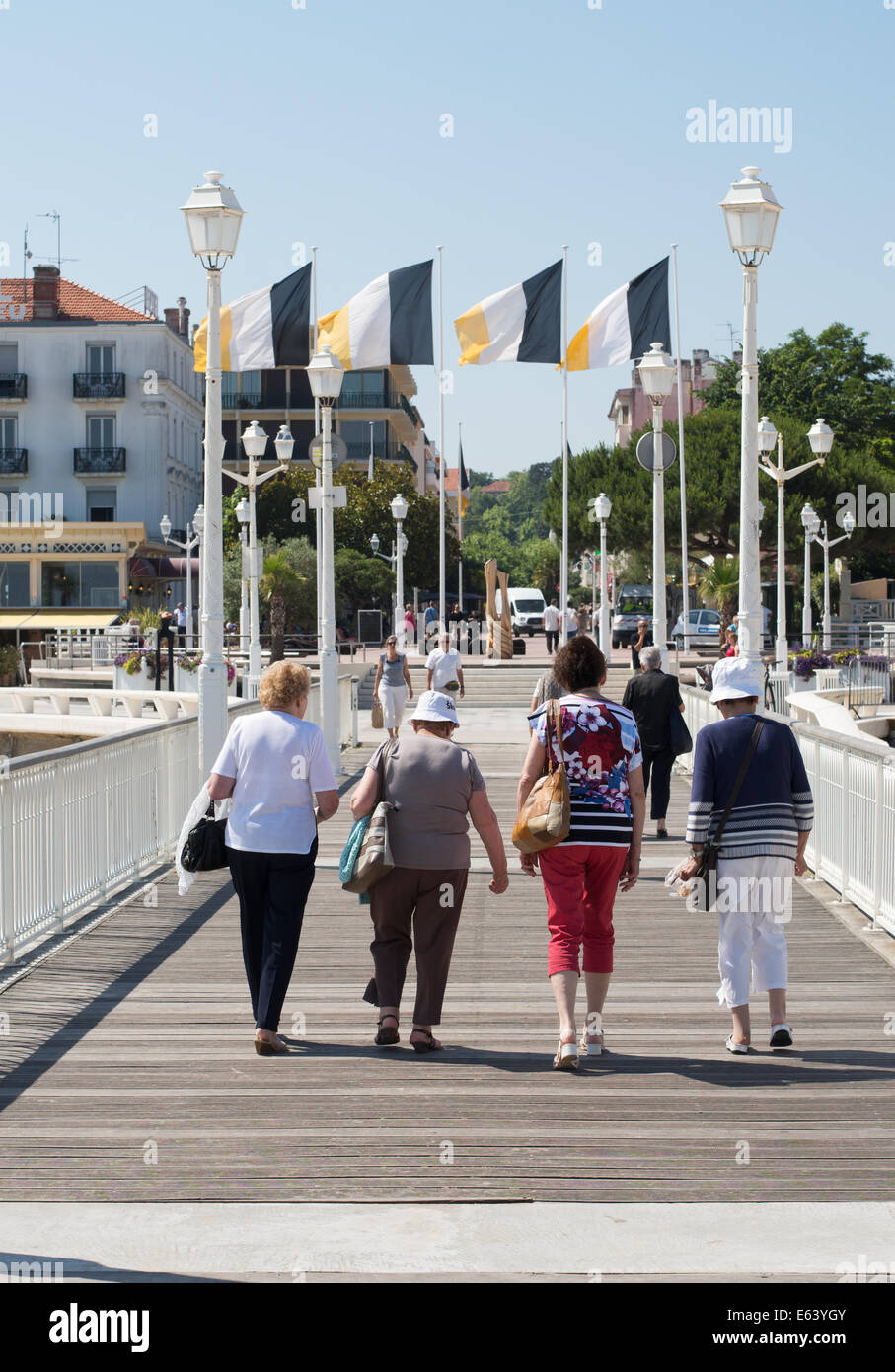 group-of-four-older-women-walking-along-
