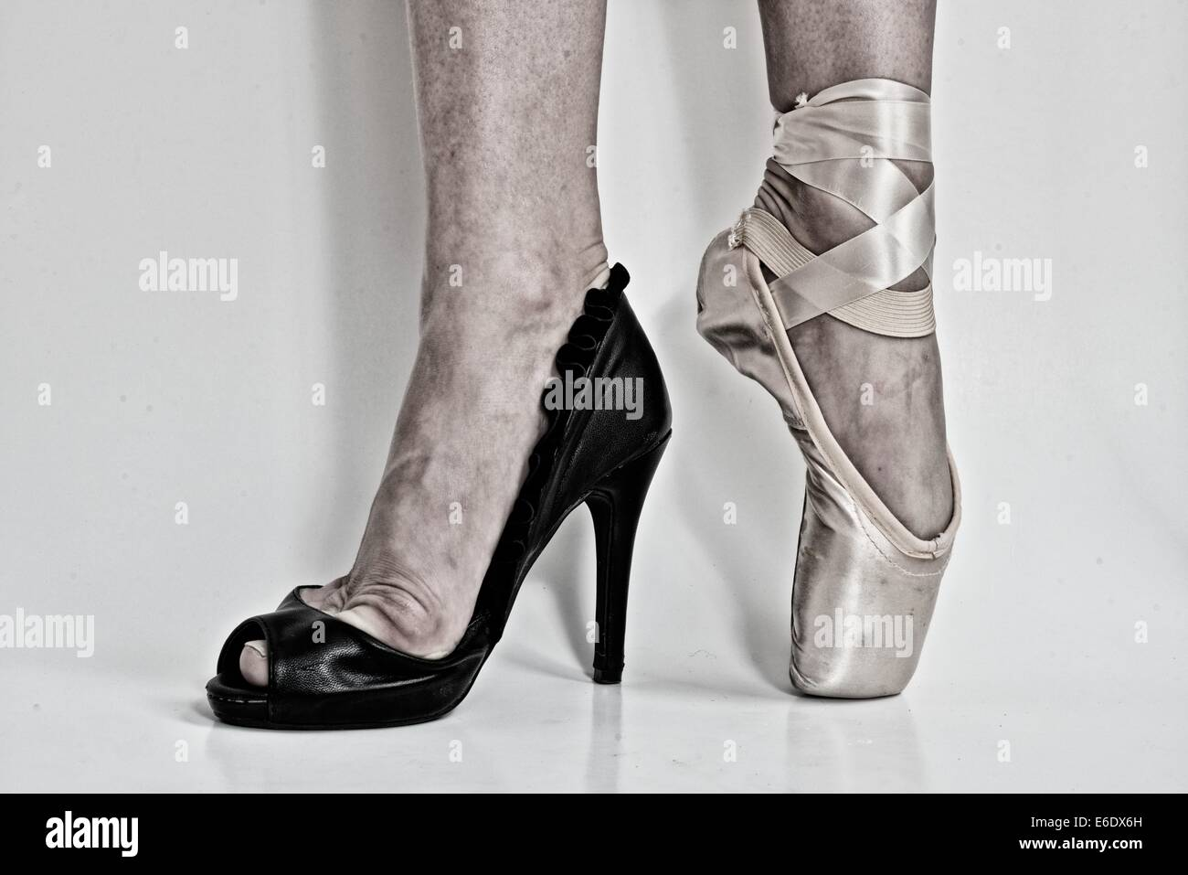 legs of a ballerina with a black high heel shoe in one