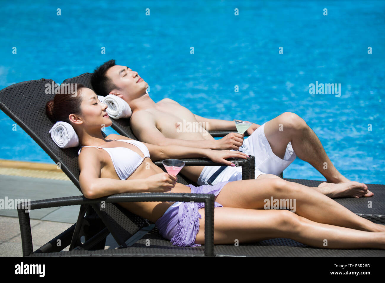 Young couple sunbathing at the poolside Stock Photo