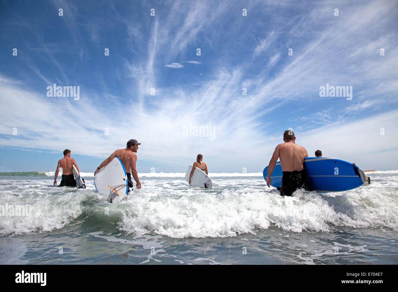 Group of male and female surfer friends wading into sea with surf boards Stock Foto