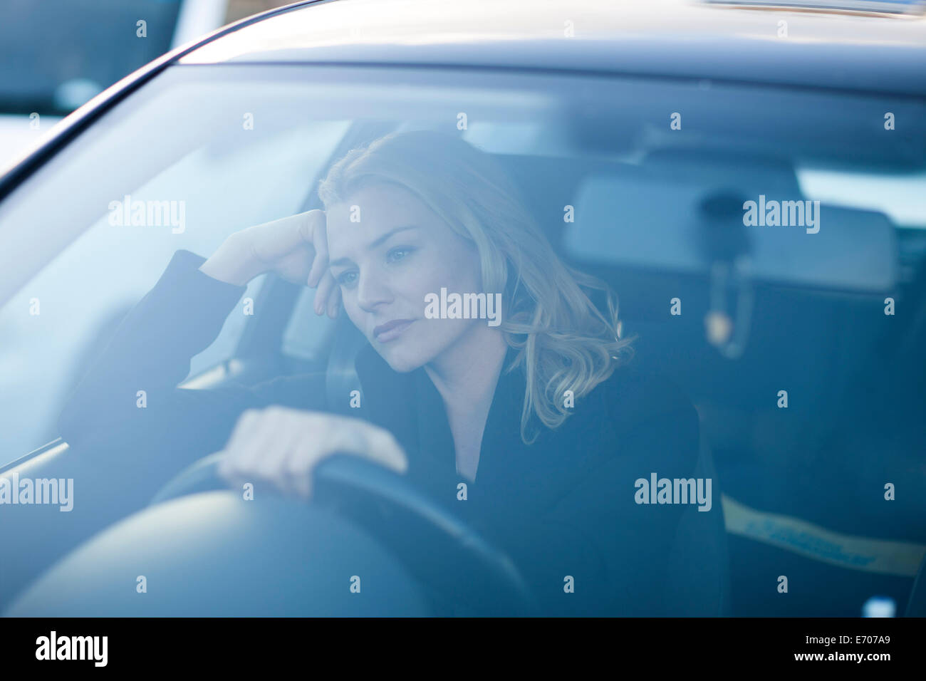 Bored businesswoman staring whilst driving in city traffic jam Stock Photo