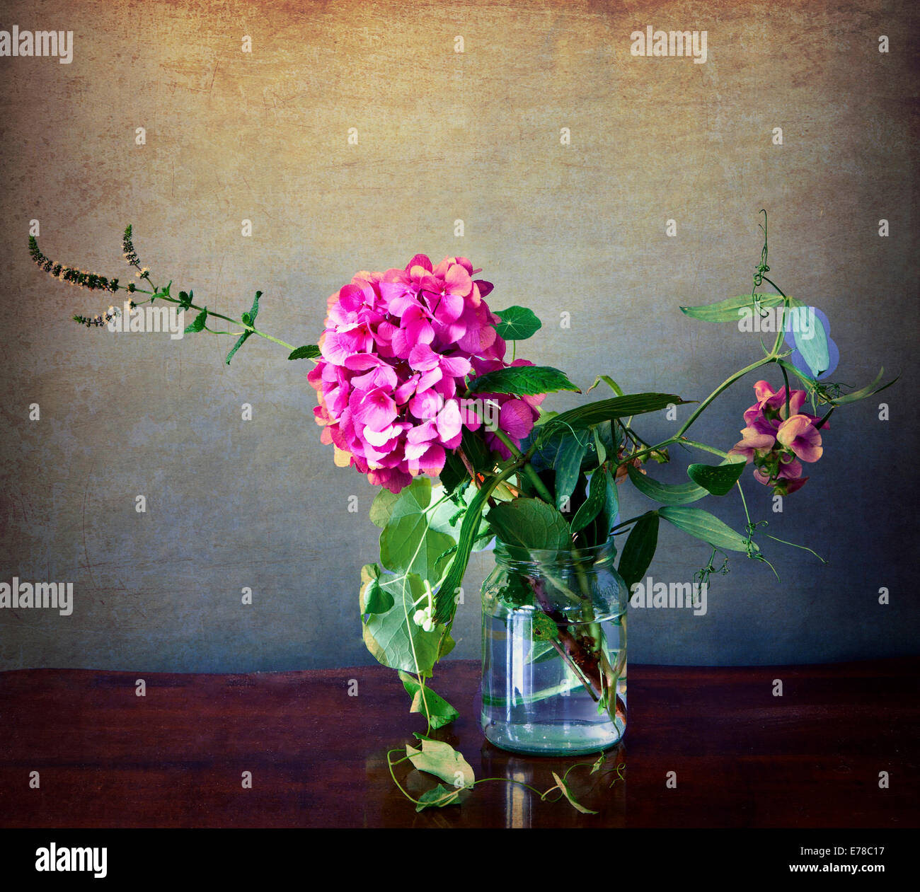 Pink hydrangea and field flowers in a glass with vintage texture and retro Instagram-like effects added Stock Photo