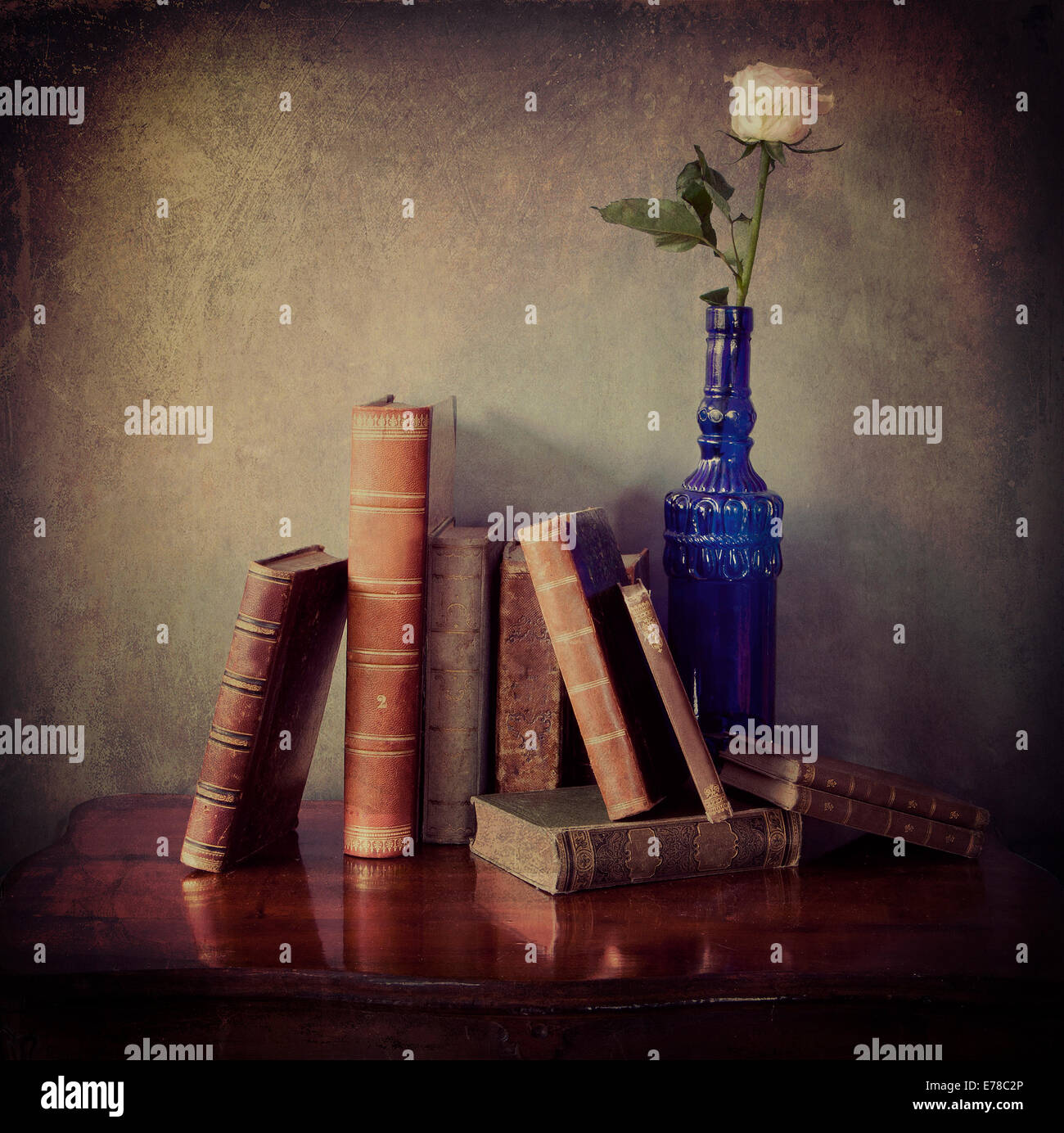 Interior still life, composition of antique books on a wooden table and a single pink rose in a blue  bottle with Stock Foto
