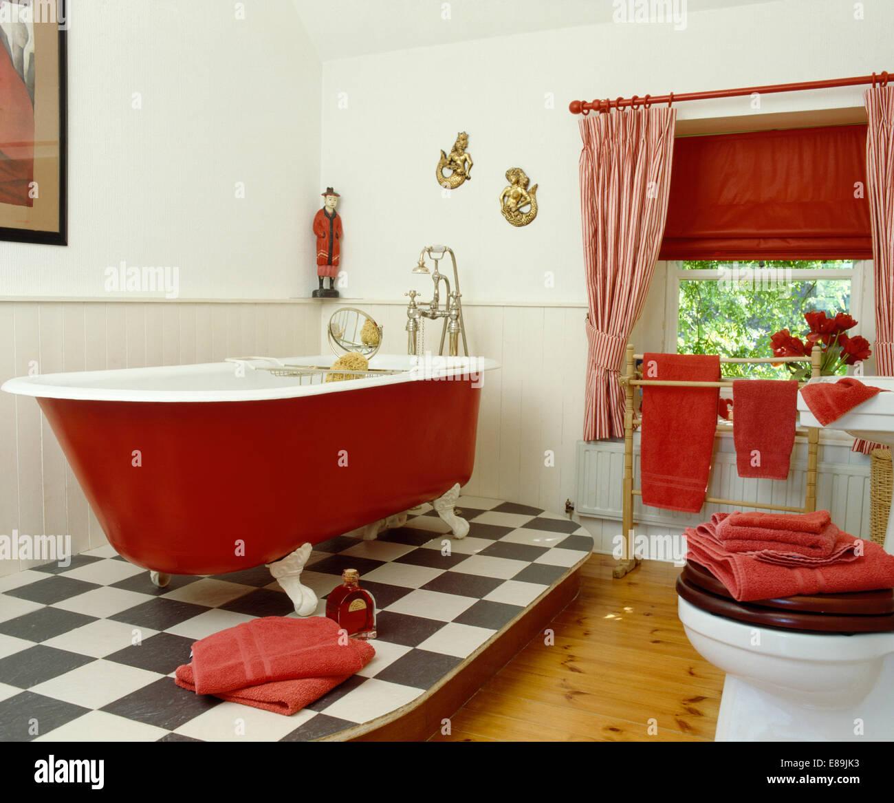 Red Rolltop Bath On Raised Black White Vinyl Floor In