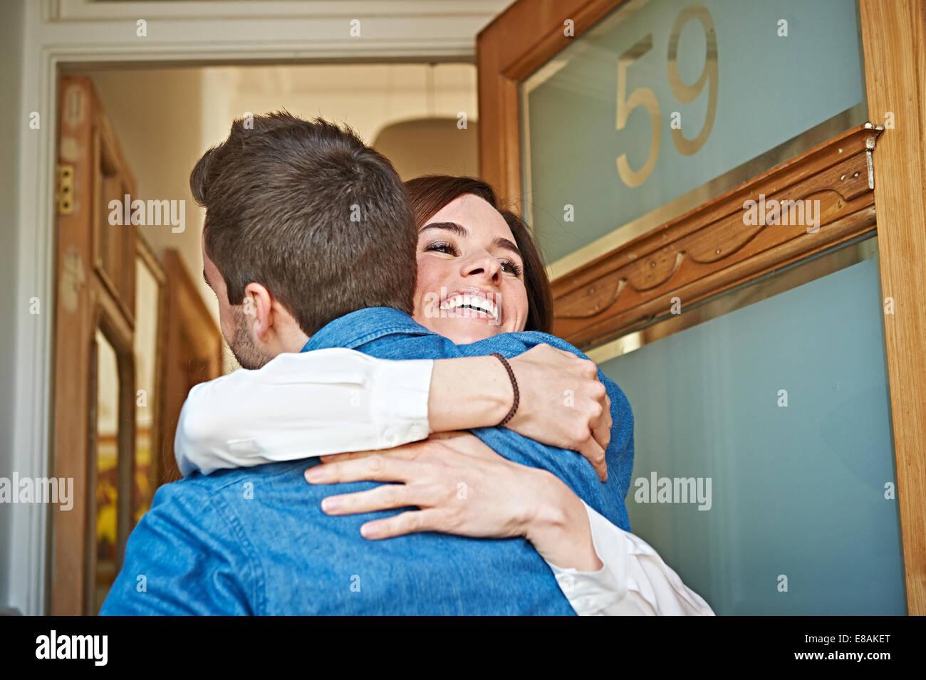 Couple hugging at front door Stock Photo