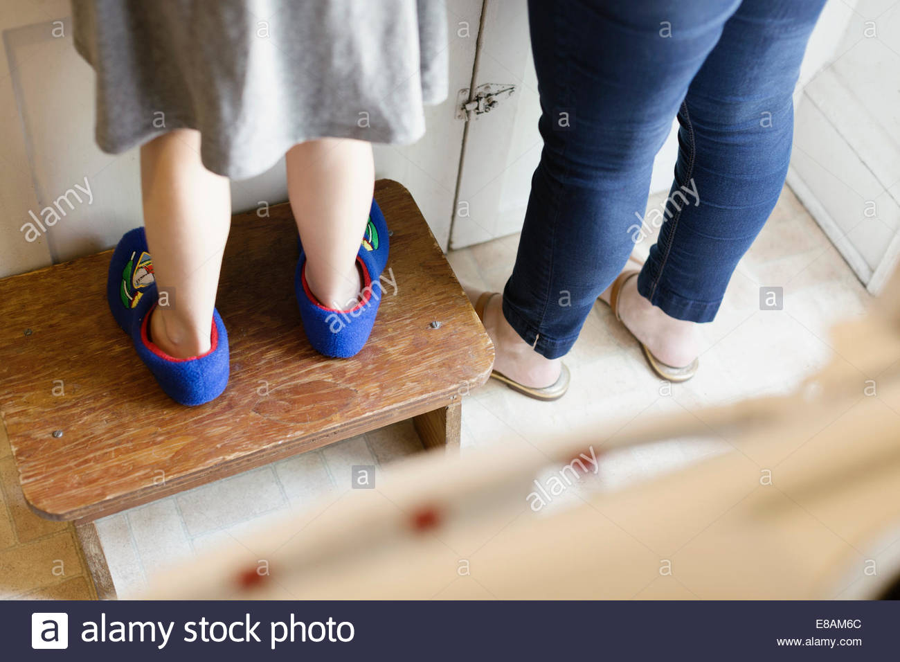 Legs of mid adult mother next to daughter standing on stool in kitchen Stock Foto