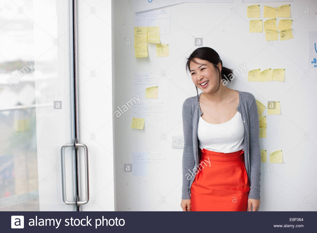 Smiling businesswoman with in front of whiteboard with adhesive notes Stock Foto