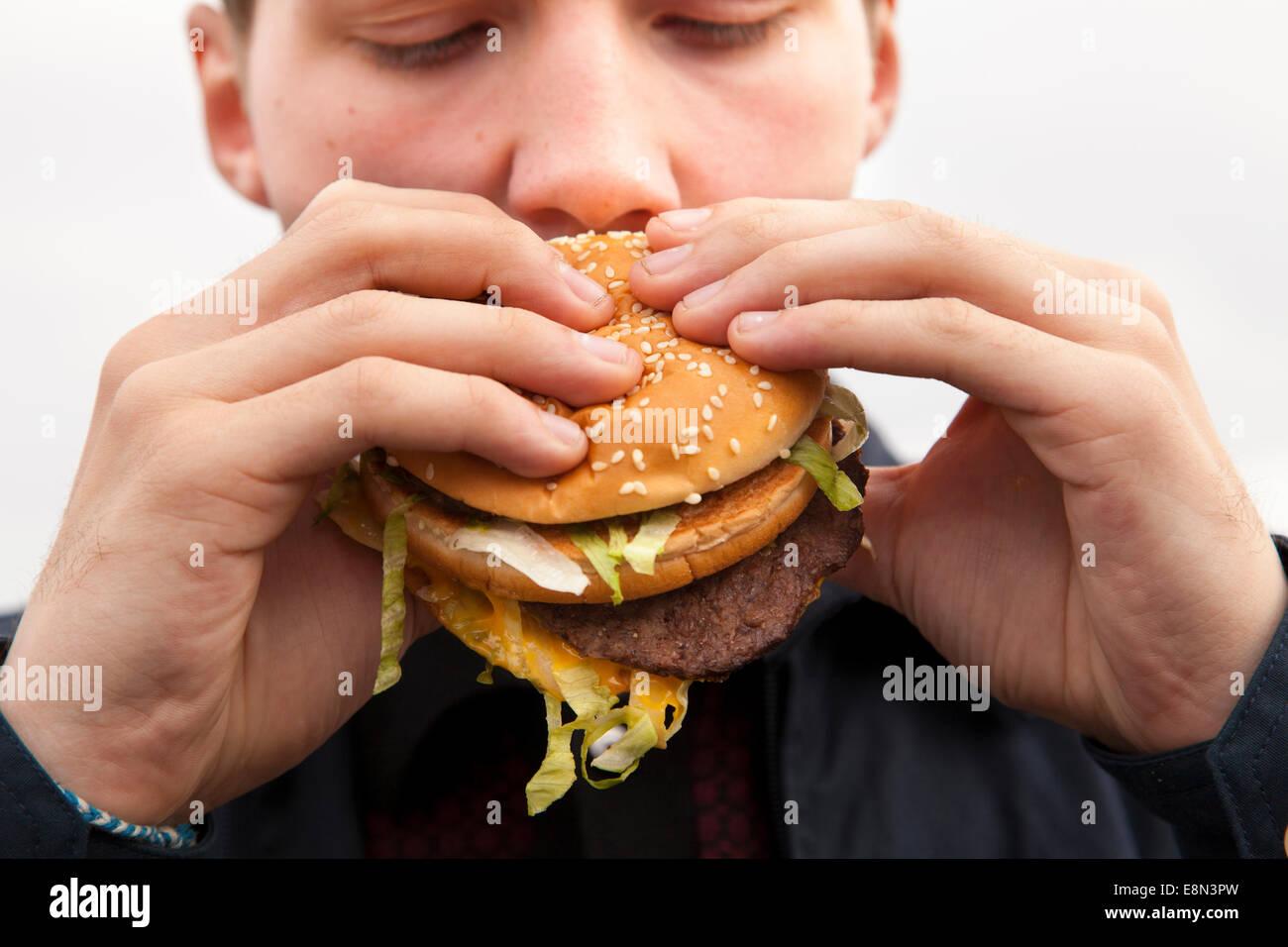 A teenager eating a McDonald's Big Mac burger. Stock Photo