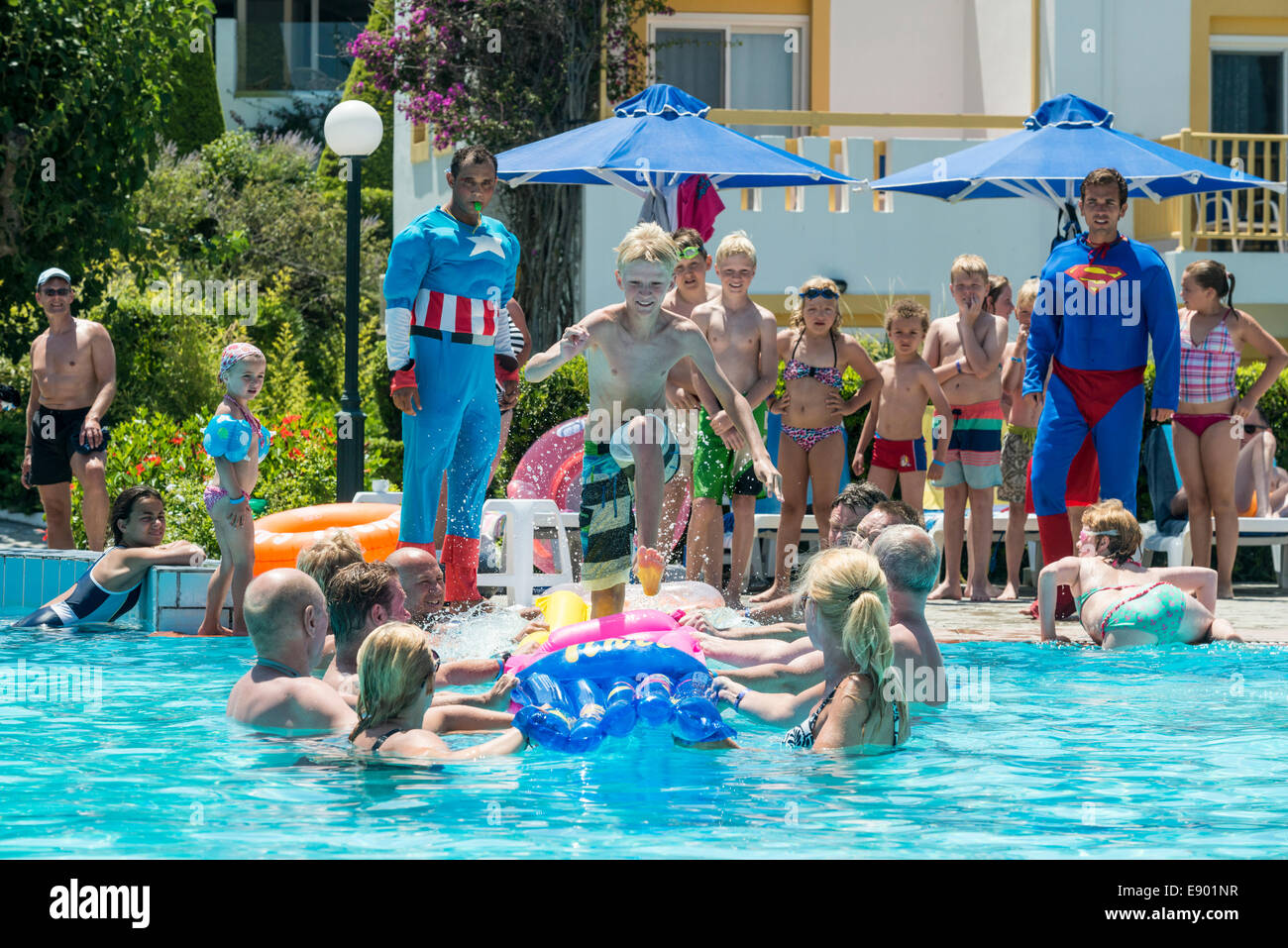 Holiday entertainers and kids playing a game in a swimming ...