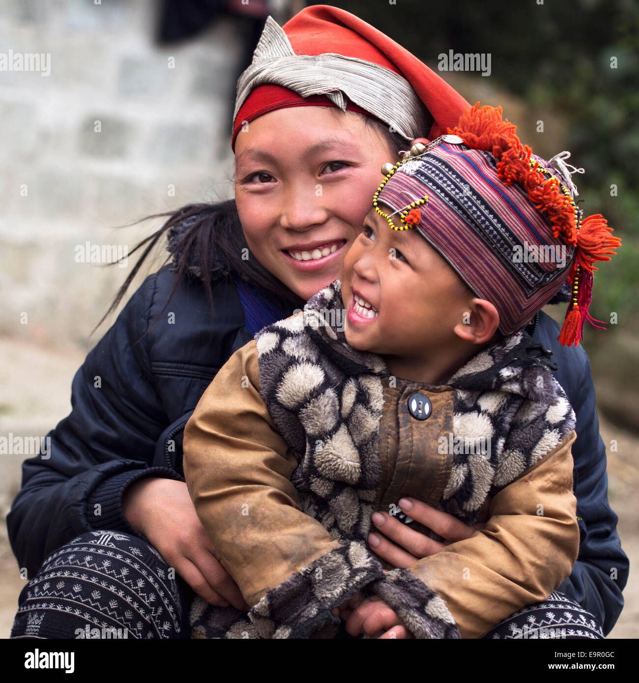 Happy Hmong woman and child smiling, sitting outside at Giang Ta Chai village near Sapa Town, Lao Cai Province, Stock Foto