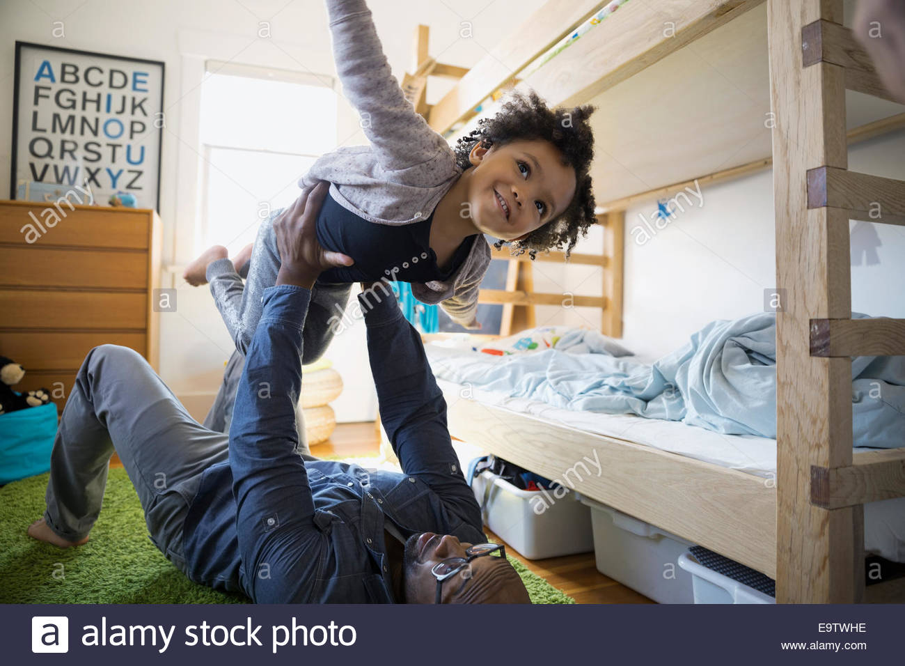 Father lifting flying daughter in bedroom Stock Foto
