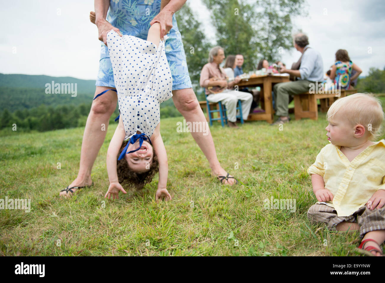 Female family member playfully holding toddler by legs at family gathering, outdoors Stock Foto