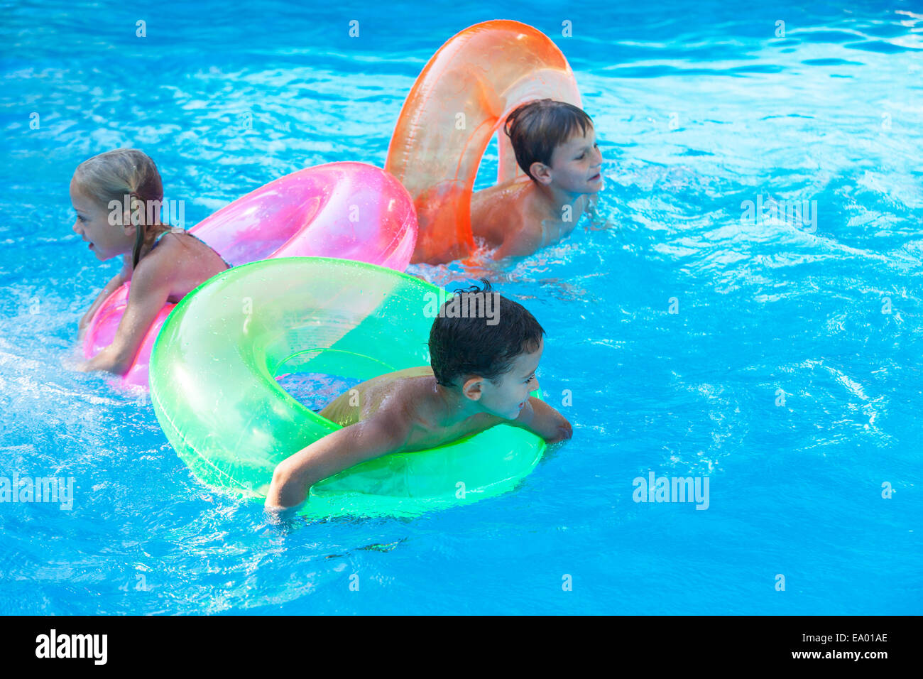 Three children playing in garden swimming pool with ...